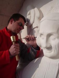 Loïc Gandrey en train de sculpté le tympan de l'église de Dardilly (69) représentant saint Jean-Marie Vianney, curé d'Ars.
